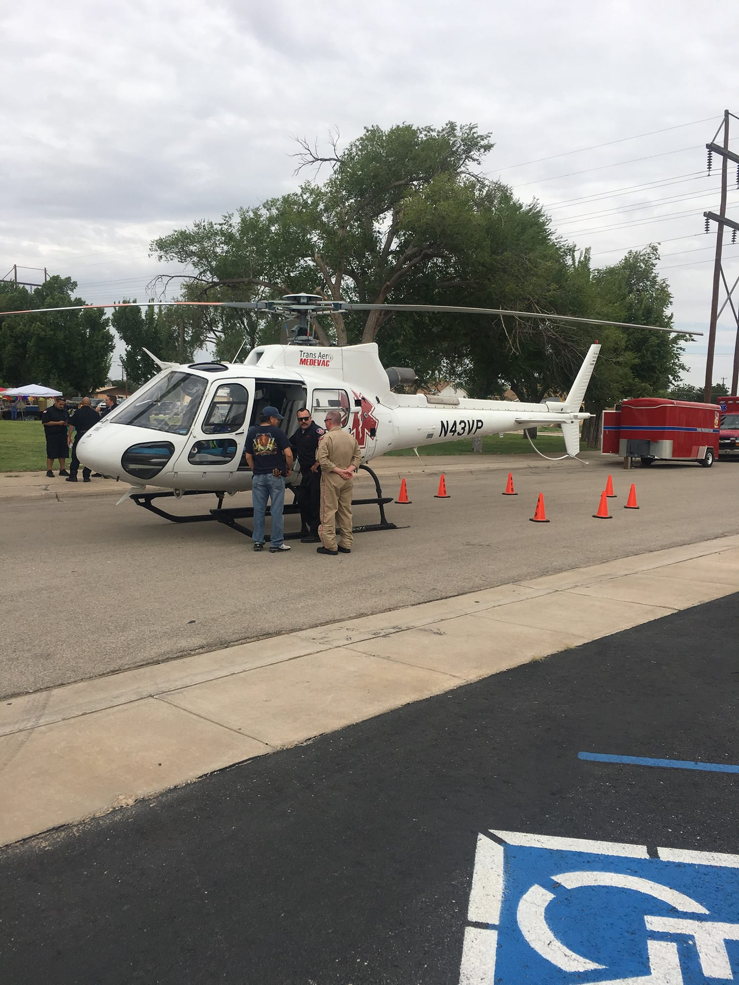 an h125 helicopter and crew sit at an event